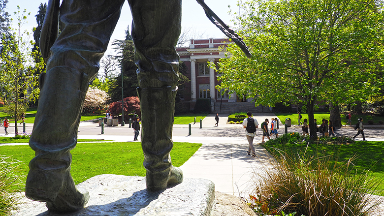 Feet of the Pioneer Father statue with people on campus